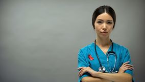 Confident asian doctor with red ribbon, international HIV AIDS awareness sign stock image