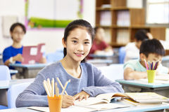 Confident asian elementary schoolgirl. Confident asian elementary school girl sitting in classroom looking at camera smiling Royalty Free Stock Image