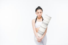 Confident asian girl in sportswear holding yoga mat and looking at camera royalty free stock image
