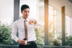 Confident asian man standing checking time and holding coffee cu. P with looking at watches at outside company Stock Photos