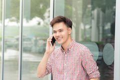 Confident asian man talking on smart phone standing outside the. Office royalty free stock image