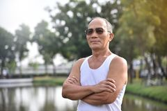 Asian Senior male posing with arms crossed. Confident Asian Senior male wear sunglasses posing with arms crossed and smiling at park outdoor background Royalty Free Stock Images