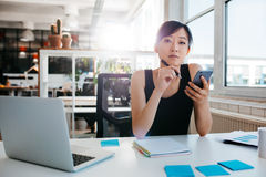 Confident asian woman sitting at her desk with mobile phone Royalty Free Stock Photos