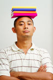 Confident asian young man with books on head Stock Photos