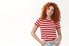Confident assertive gorgeous curly-haired redhead woman hold hands pockets self-assured smiling tilting head wearing. Striped summer t-shirt enthusiastic stock photography