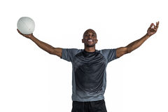 Confident athlete with arms raised holding rugby ball Stock Photo