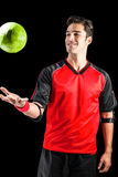 Confident athlete man playing with a ball. On black background Royalty Free Stock Images