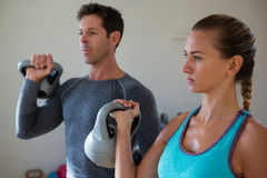 Confident athletes exercising with kettlebells. In gym Royalty Free Stock Photos