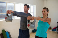 Confident athletes lifting kettlebells. In club Stock Photography