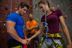 Confident athletes preparing for wall climbing. In gym Royalty Free Stock Photos