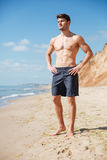 Confident athletic young man standing on the beach Royalty Free Stock Images