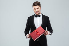 Confident attracive man in tuxedo standing and holding gift box Stock Images