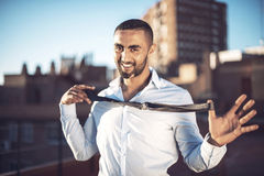 Confident attractive Arab businessman undressing Royalty Free Stock Photo