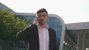 Confident attractive bearded businessman talking by phone and solving his business deals. Glass airport wall background.  stock video footage
