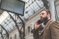 Confident attractive businessman dressed in stylish clothes using mobile phone hand at the hall of railway station and stock photos