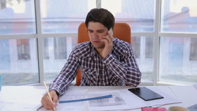 A confident and attractive businessman working with blueprints, talking phone in a light, modern office. Business