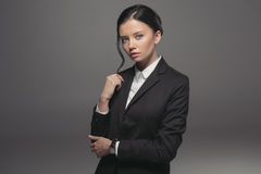 Confident attractive businesswoman wearing black suit and looking at camera Royalty Free Stock Images