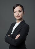 Confident attractive female manager posing. Confident female manager posing with arms crossed on gray background Stock Image