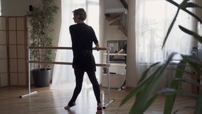 Flexible mature woman dancing at home in front of the mirror. Elegant slim woman in black clothes doing exercises. Confident attractive mature ballerina with stock footage