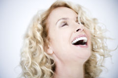 A confident and attractive middle-aged woman in white, laughing Stock Photo