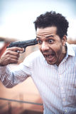 Confident attractive mulatto man with a gun royalty free stock photos