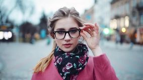 Confident attractive woman moving right towards the camera, looking around, touching her glasses. Trendy look. Urban. Settings on the background. Perfect stock footage