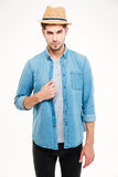 Confident attractive young man in blue shirt and hat Royalty Free Stock Image