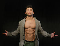 Confident, attractive young man with open jacket on muscular torso. Ripped abs and pecs. Arms open Royalty Free Stock Image