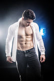 Confident, attractive young man with open shirt on. Muscular torso, ripped abs and pecs. On dark background with spotlights behind him Stock Images