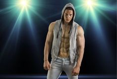 Confident, attractive young man with open vest on. Muscular torso, ripped abs and pecs. On dark background with spotlights above Royalty Free Stock Photos