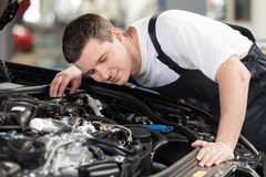 Confident auto mechanic. Confident mechanic listening to the car engine working stock photos