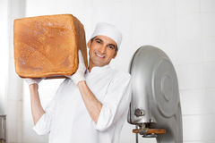 Confident Baker Carrying Big Bread Loaf On Shoulder In Bakery stock image