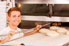 Confident baker. Confident young male baker putting dough into the oven and smiling Stock Photo