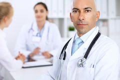 Confident bald  doctor man   with medical staff at the hospital. Confident bald doctor men with medical staff at the hospital Royalty Free Stock Image