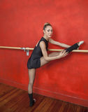 Confident Ballerina With Leg On Bar In Studio Royalty Free Stock Image
