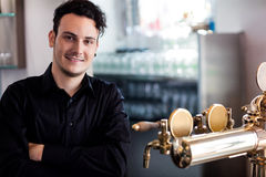 Confident bartender standing at bar counter. Portrait of young confident bartender standing at bar counter Royalty Free Stock Photo