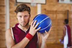 Confident basketball player holding basketball in the court. Portrait of confident basketball player holding basketball in the court Royalty Free Stock Photo