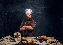 A bearded baker wearing a uniform standing with his arms crossed next to a table, decorated with delicious bread loaves. Confident bearded baker wearing a stock photo