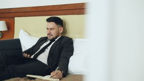 Confident businessman lying on bed using laptop computer and writing notes at notepad while working in hotel room. Confident bearded businessman lying on bed stock video footage