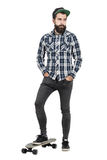 Confident bearded hipster with baseball cap standing on skate board looking down Royalty Free Stock Photo