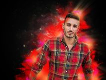 Hipster young man in burning explosion effect. Confident bearded hipster man in casual outfit looking at camera in burning flame effect stock images