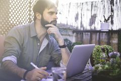 Confident Bearded Man sitting at vintage natural rough wood desk working on laptop computer at cafe terrace surrounded. Green flores and cactus.Out of office stock image