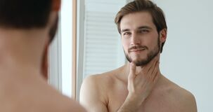 Confident bearded man applying aftershave lotion on face and neck