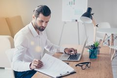 Confident bearded stylish concentrated businessman in white shirt works in lightful office with documents while sitting at the ta stock images