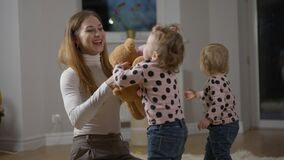 Confident beautiful Caucasian woman singing dancing in slow motion playing with twin daughters indoors. Happy joyful