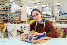 Beautiful woman designer using tailor machine Stock Image