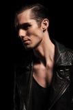 Confident biker in leather jacket posing in dark studio. Close portrait of confident biker in black leather jacket posing in dark studio background looking away Royalty Free Stock Images