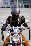 Confident biker a man or a guy-racer in a protective helmet sits on a classic-style motorcycle, looking away, in the Parking lot royalty free stock photo