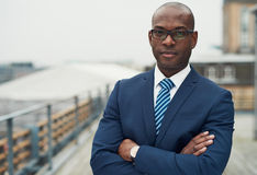 Confident black business man. In a stylish suit, standing with folded arms on a rooftop of n office block looking at the camera with a serious expression Stock Photos
