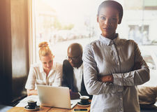 Confident black business woman. Confident black business women standing in front of colleagues stock images